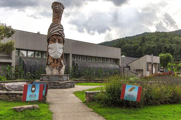 Cherokee-intiaanimuseon edustalla oleva toteemi oli puettu kasvomaskiin Pohjois-Carolinassa elokuussa 2020.