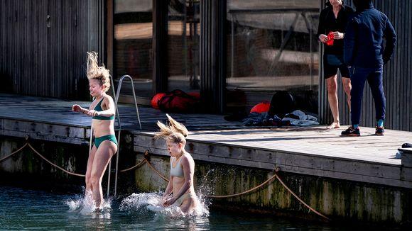 Kaksi nuorta hyppää satamalaiturilta meriveteen Kööpenhaminassa.