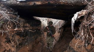 Ukrainalaissotilas kävelee juoksuhaudassa Avdiivkan alueella Donetskissa.