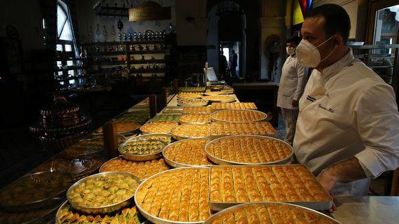 Kuvassa myyntipöydällä on Baklava-leivonnaisia. Pöydän takana seisoo kaksi miestä, jotka ovat leipomon työntekijöitä.