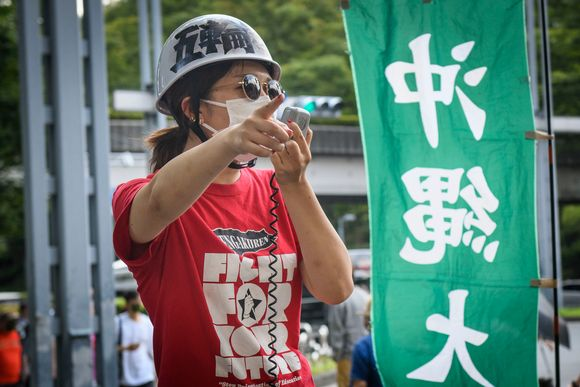 Opiskelijat osoittivat mieltään Tokion olympialaisia vastaan kaupungintalon edessä.