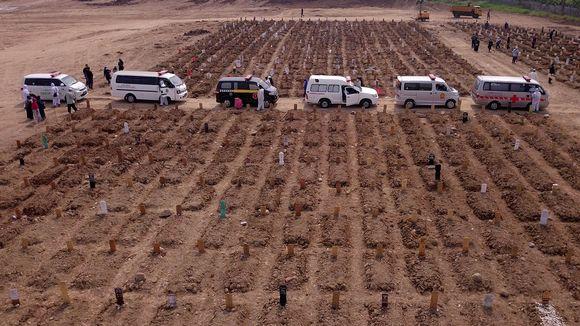 Viisi ambulanssia rivissä, edustalla tuoreita hautoja.