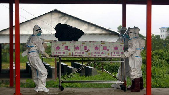 Kolme suojapukuihin pukeutunutta vapaaehtoista kuljettaa arkkua paareilla. Arkun ympärille kiedottu vaalenpunaisilla sydämillä koristettua paperia.