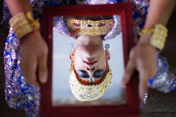 Hindujumalaksi meikattu lapsi katsoo peiliin ennen osallistumistaan Hindujen Janmashtami-juhlaan Intian Amritsarissa