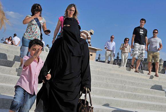 Niqabia käyttävä nainen kävelee lapsen kanssa.