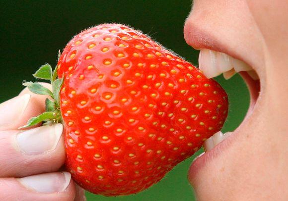 Nainen haukkaa mansikkaa