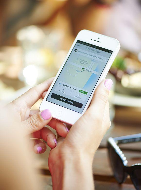 Henkilö käyttää Uber-sovellusta älypuhelimella.