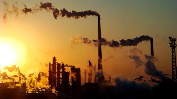 tehtaan piipuista tupruaa savua.