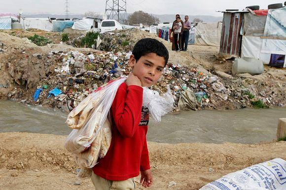 Pikkupoika, jonka olalla on muovikasseja, kulkee telttakylän tunkiokasan editse.