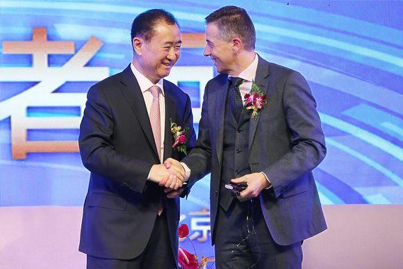 Wang Jianlin vasemmalla kättelee Philippe Blatteria.