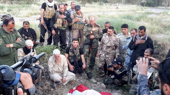 Joukko sotilaita seisoo ruohikkoisessa maastossa haudan edessä päät painuksissa, monet pitävät toista kättään rinnallaan kunnioituksen osoituksena. Osalla miehistä on maastopuvut, osalla siviilivaatteet, osalla mustat puvut. Haudalla on ilmeisesti Irakin lippu.