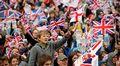 Suuri ihmisjoukko heiluttaa Britannian ja Eglannin lippuja.