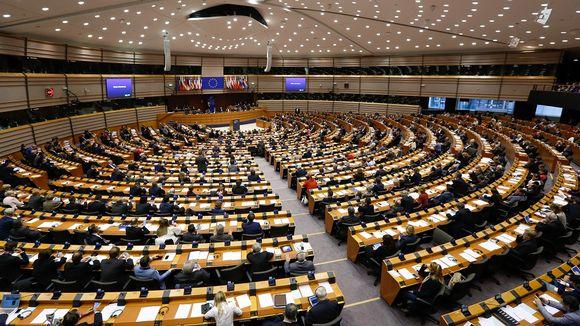 Jietna: Kuva Euroopan parlamentin istuntosalista, jossa edustajien pöydät levittäytyvät puheenjohtajan korokkeesta. Puheenjohtajan korokkeen yllä on EU:n lippu ja jäsenvaltioiden liput.
