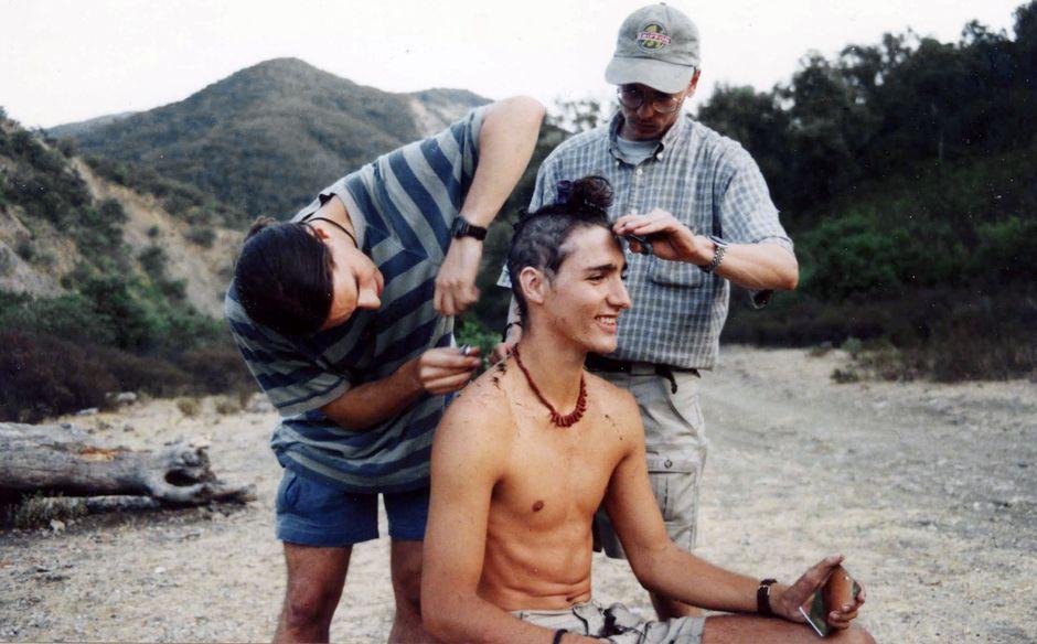 Kaksi nuorta miestä leikkaa nuorelta Justin Trudeaulta hiuksia ulkoilmassa, taustalla näkyy rinnettä ja metsää.