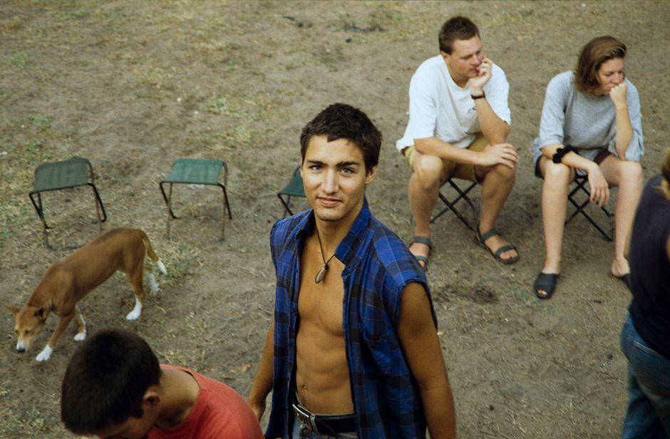 Justin Trudeau hymyilee kameralle taustallaan leirijakkaroita, joilla istuu kaksi ihmistä.