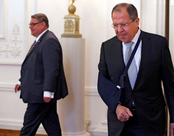 Timo Soini ja Sergei Lavrov kävelevät eri suuntiin. Lavrovilla on käsi paketissa.