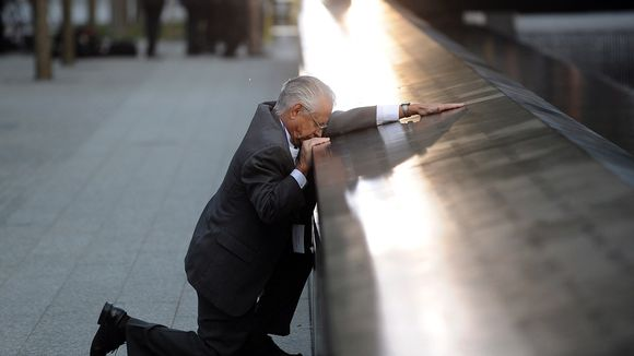 Toisen polvensa varaan laskeutunut vanha mies pitää kättään matalan muurin päällä.