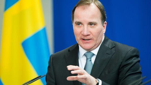 Puolikuva Löfvenistä tummassa puvussa. Taustalla Ruotsin lippu.