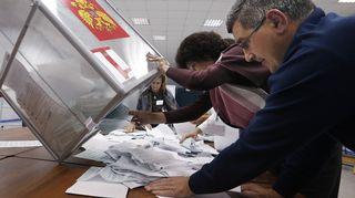 Ääntenlaskijat aloittavat työnsä kääntämällä äänestylippulaatikon nurin.