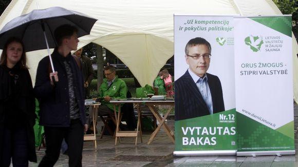 Vaalimainos ja sen takana kampanjateltta. Edessä ohikulkijoita sateenvarjon alla.
