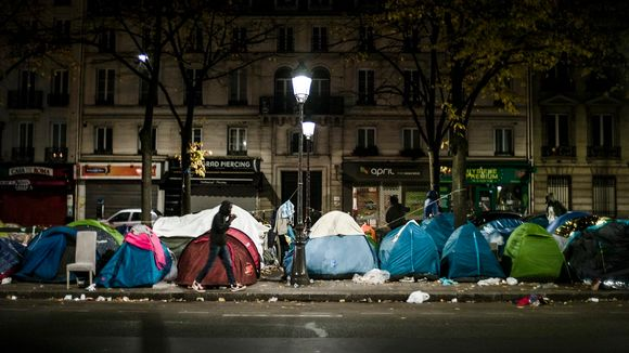 Telttoja vieri vieressä roskaisella kadulla.