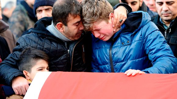 Mies ja kaksi poikaa surevat lipulla peitetyn arkun äärellä.
