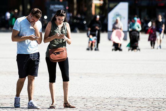 Pariskunta kännyköineen Pariisin Parc de la Villette'ssa.
