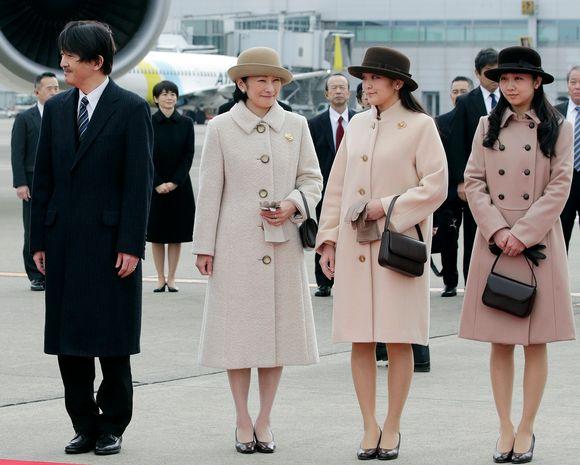 Prinsessa Mako vaalenruskeassa takissa ja tummanruskeassa hatussa Tokion lentokentällä vanhempiensa ja sisarensa kanssa.