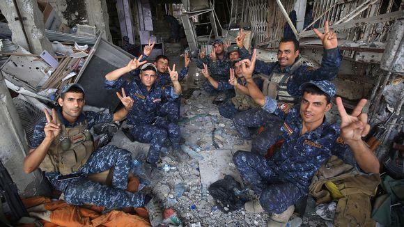 Irakin poliisivoimien jäsenet näyttävät voitonmerkkiä.