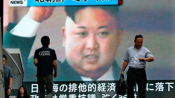 Miehet kävelevät tv-screenin ohi, jossa näkyy Kim Jong-Unin kasvot.