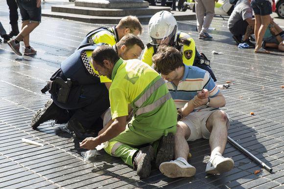 Poliisit auttoivat loukkaantunutta La Ramblalla torstaina.
