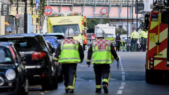 Kaksi palomiestä ja ambulansseja kadulla.