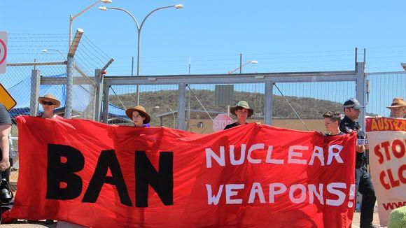 Joukko aktivisteja seisoo tukikohdan portilla pitäen käsissään punaista lakanaa, jossa lukee englanniksi: Kieltäkää ydinaseet.