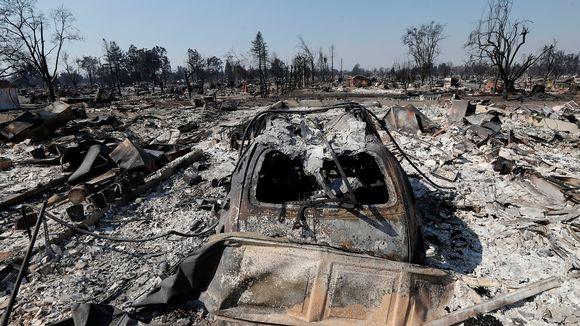 Palon jäljiltä tuhkan peitossa olevaa maisemaa. Etualalla on palossa tuhoutunut pick-up-auto.