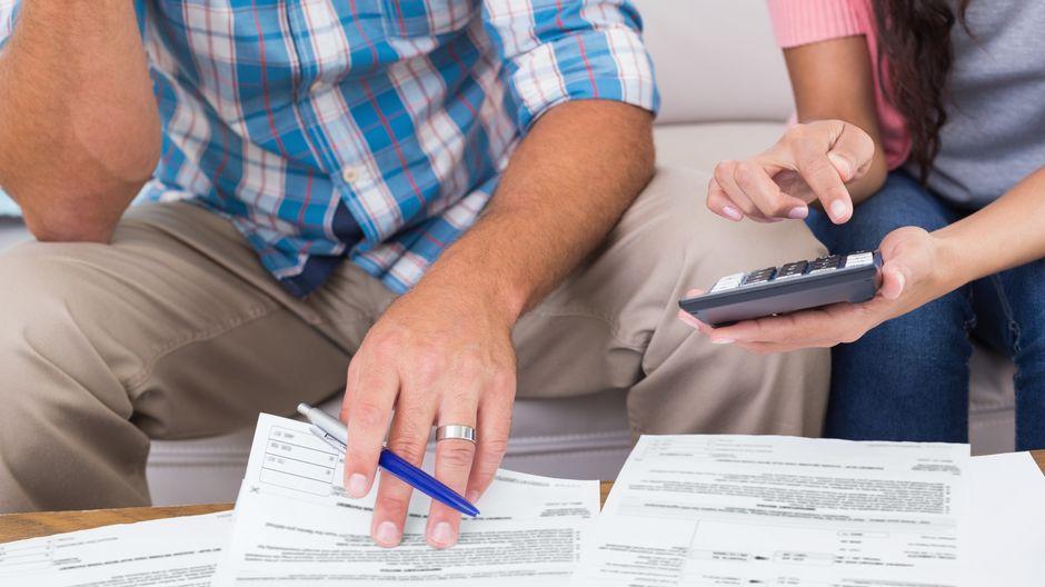 En man och en kvinna sitter och tittar på finanspapper med penna och miniräknare i hand.