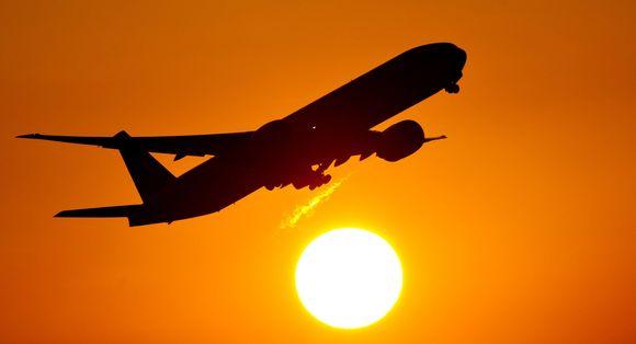 Lentokone nousee taivaalle oranssinkeltaista taivasta ja aurinkoa vasten.