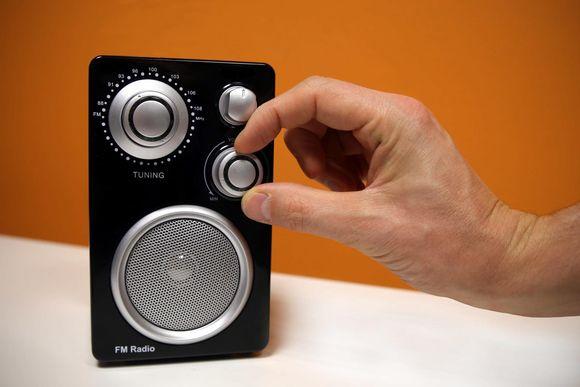 Mies säätää radion äänenvoimakkuutta.