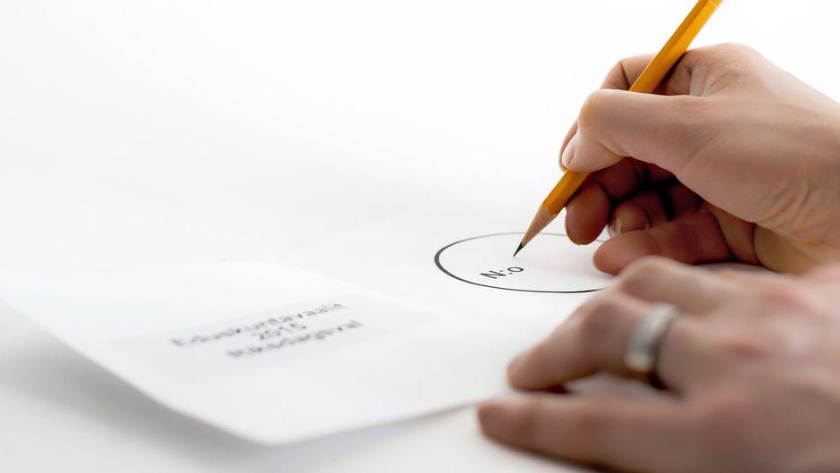 Nainen kirjoittamassa ehdokkaansa numeroa äänestyslipukkeeseen.
