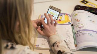 Kännykkä lapsen kädessä koulussa