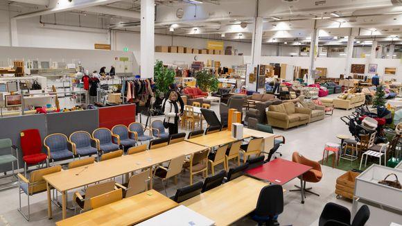 Laajakuva kierrätyskeskuksessa, etualalla pöytiä ja tuoleja.