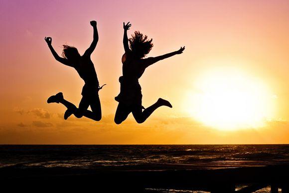 Kaksi ihmistä hyppää ilmaan iloisesti rannalla auringonlaskua vasten