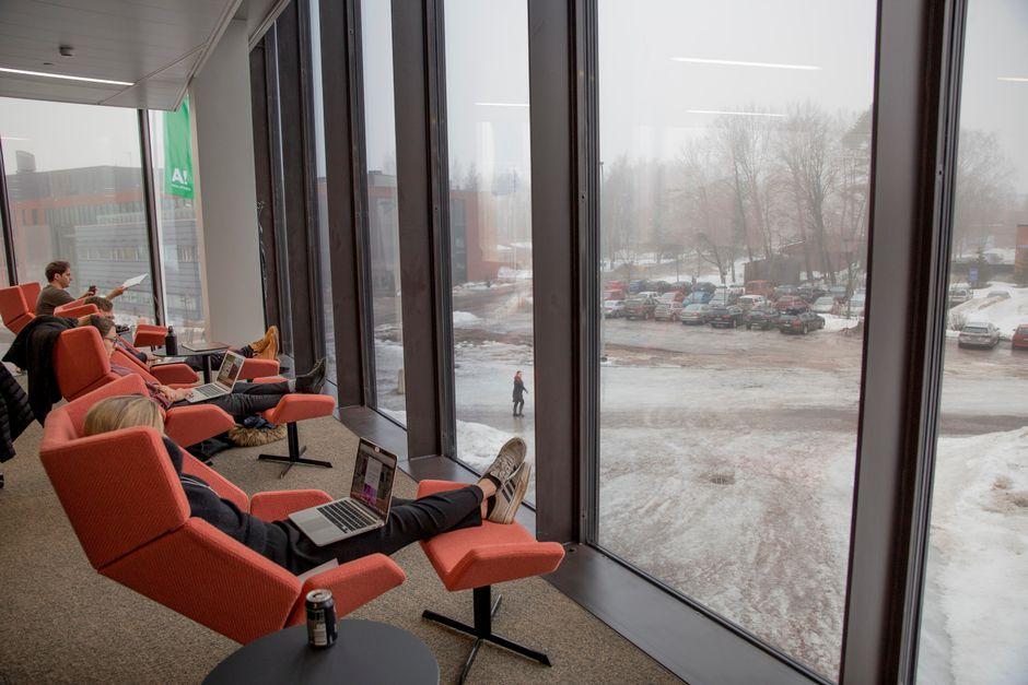 Aalto-yliopiston kauppakorkeakoulun opiskelijoita istumassa tietokoneiden kanssa nojatuoleissa lasiseinän edustalla.