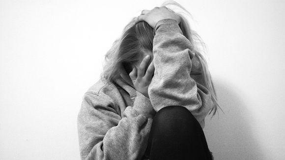 Tyttö istuu nurkassa ja on peittänyt kasvonsa käsiinsä.