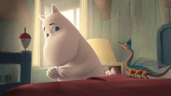 Muumipeikko istuu sängyllään, vieressä pieni lohikäärme.
