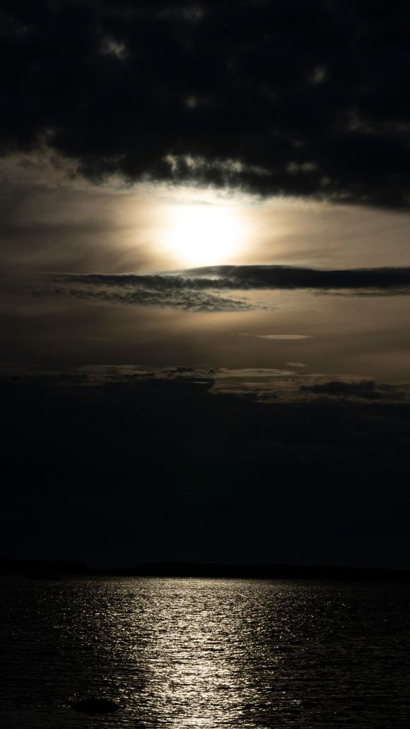 Synkkä auringonlasku meren yllä.
