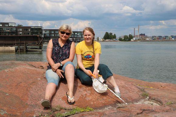 Susa Österlund-Toivonen och Eeva Puustjärvi sitter på en strandklippa på Drumsö