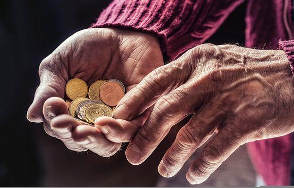 Kolikoita vanhan ihmisen kädessä.