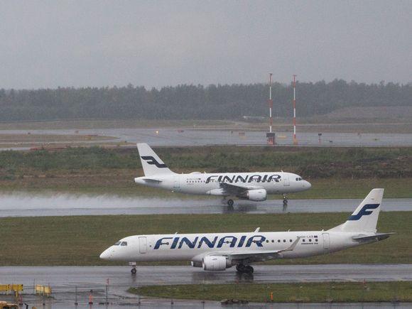 Kaksi Finnairin lentokonetta Helsinki-Vantaan lentoasemalla. Toinen on juuri nousemaassa.