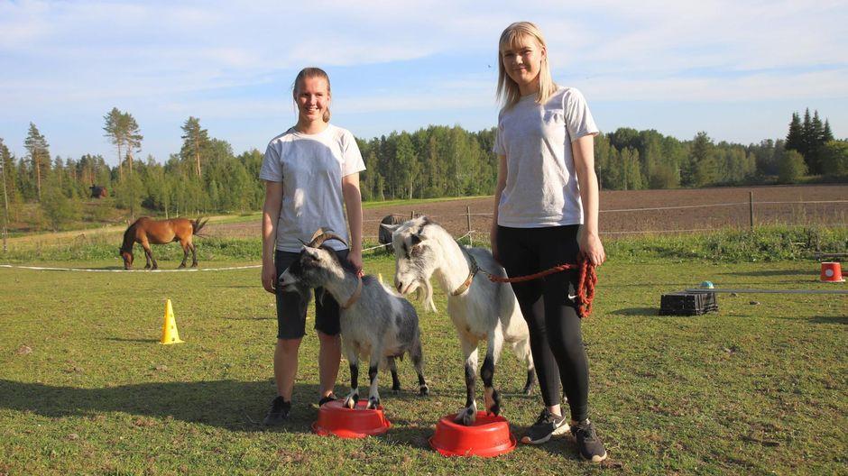 Henna Kerkelä ja Vilma Kotro poseeraavat vuohien kanssa.