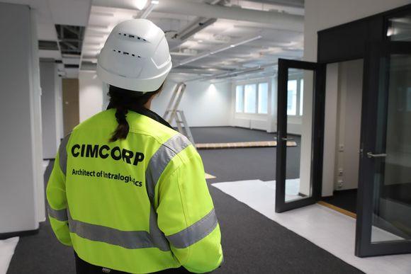 Cimcorpin työntekijä katsoo tyhjää toimistotilaa kypärä päässä.